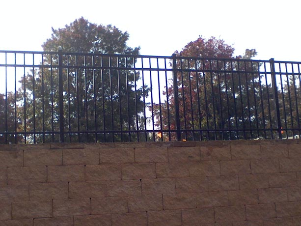 Aluminum Fence Installed over a Stone Wall By Phoenix Fence And Deck