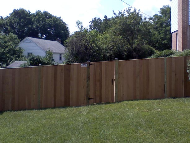 Board and batton fence with gate built on a sloped yard